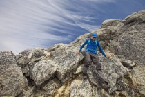 Photograph of backpacker descending rocks at Needle Peak, Hope, British Columbia, Canada — Stock Photo