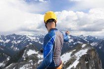 Photograph of mountain climber in safety helmet photographing view from summit of mountain in North Cascade Mountain Range, Chilliwack, British Columbia, Canada — Stock Photo