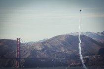 Photograph of stunt plane flying and leaving smoke trail near Golden Gate Bridge, San Francisco, California, USA — Stock Photo