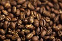 Gros plan de tir des grains de café fraîchement torréfiés bruns — Photo de stock