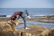 Woman doing yoga on rocky coastline — Stock Photo