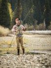 Homme en ajustant la canne à mouche alors qu'il pêchait près de Mccall, Idaho — Photo de stock