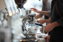 Side view of baristas preparing coffee with coffee maker, Oakland, California, USA — Stock Photo
