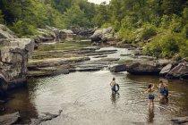 Three young women walking in river — Stock Photo