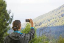 Female Hiker Taking Picture Of Mountain With Smartphone — Stock Photo