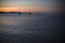 Sailboats at sunrise in Cala Goloritz — Stock Photo