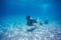 Homem andando com pedra debaixo d'água. — Fotografia de Stock