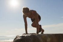 Woman Doing Exercise On Boulder Near Beach — Stock Photo