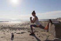 Женщина делает растяжки на пляже — стоковое фото
