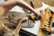 Young woman carving picture on wood — Stock Photo