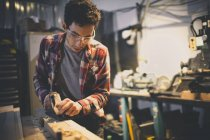 Carpenter working on piece of wood with hand planer. — Stock Photo