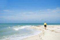 Вид сзади женщину ходить на пляже — стоковое фото
