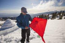 Un escursionista in procinto di volare un aquilone sulla cima di una neve coperto montagna — Foto stock