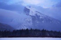 Вершина гори з хмар позаду сніг покриті озеро — стокове фото
