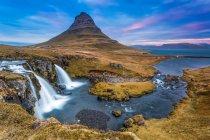 Cascata e fiume con la montagna sullo sfondo — Foto stock