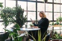 Tomando un descanso y leyendo desde el teléfono en la tienda de plantas lindo - foto de stock