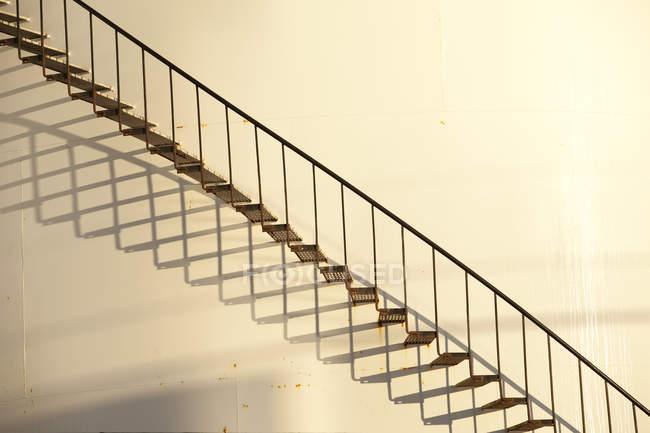 Крупным планом вид лестницы белой стене с тенью — стоковое фото