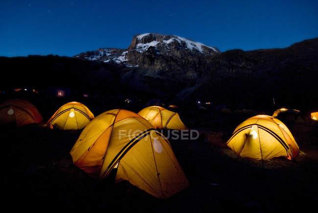 Живописный вид палатки ночью с горы на фоне — стоковое фото