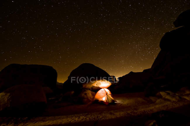 Tent illuminating the night landscape, Joshua Tree National Monument, USA — Stock Photo
