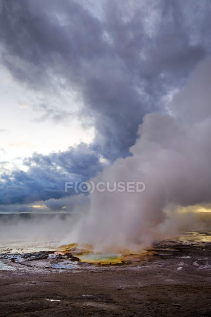 Clepsydra Geyser erupts at sunset in the Lower Geyser Basin of Yellowstone National Park, Wyoming — Stock Photo