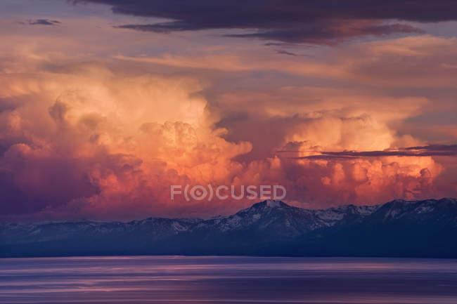 Couvert de nuages orageux Alpenglow au coucher de soleil sur le lac Tahoe et la neige montagnes de la Sierra — Photo de stock