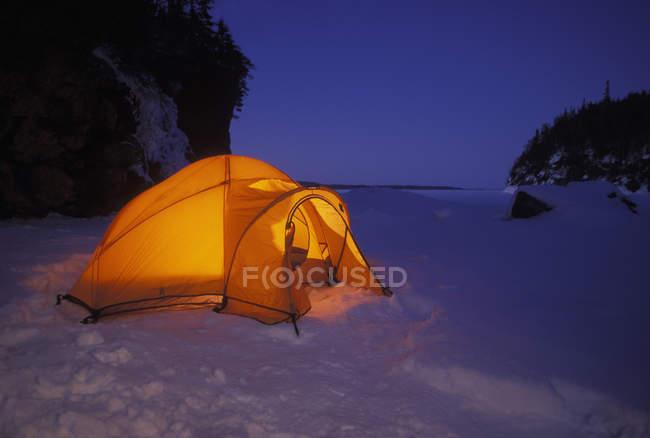 Aglow Orange Zelt auf dem Schnee bedeckt See in der Abenddämmerung von Klippen geschützt. Im Hintergrund ist eine Öffnung zum Abenteuer — Stockfoto