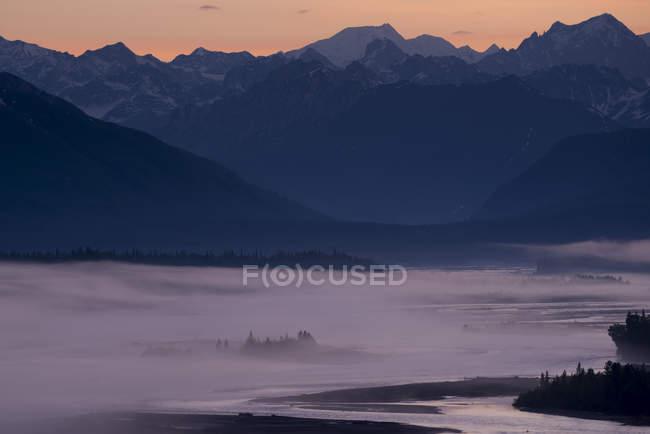 Тонкий слой тумане blanketed реку и вечнозеленые с горы на заднем плане на закате, Национальный Парк Денали, Аляска, США — стоковое фото
