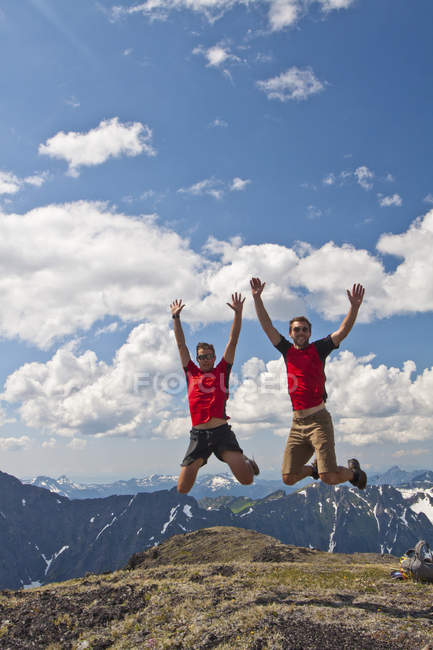 Two hikers wearing red shirts jump in an alpine meadow. — Stock Photo