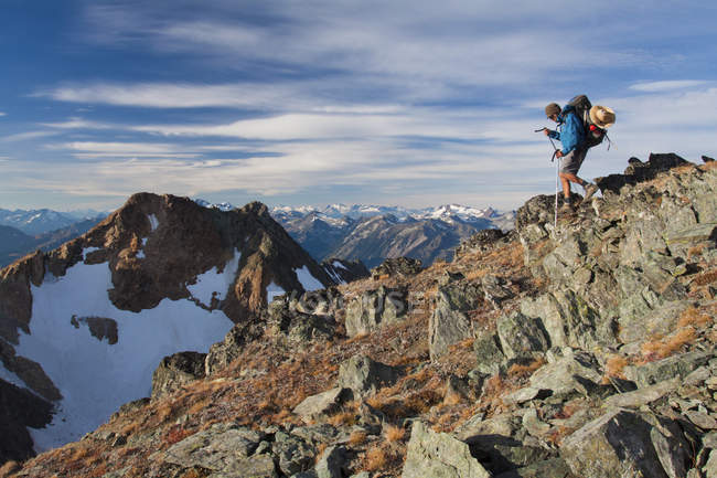 A hiker descends from the summit of Crystal Peak near Pemberton, British Columbia, Canada. — Stock Photo