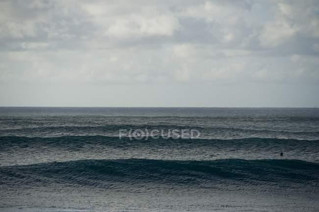 Живописный вид волн ролл из-за горизонта — стоковое фото