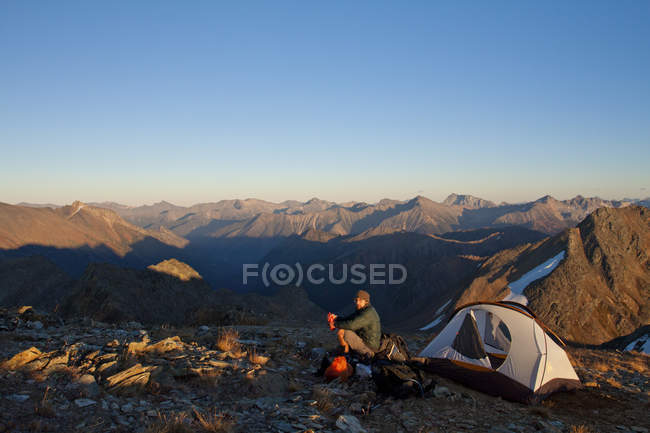 A hiker sits beside his tent on the summit of Crystal Peak near Pemberton, British Columbia, Canada. — Stock Photo
