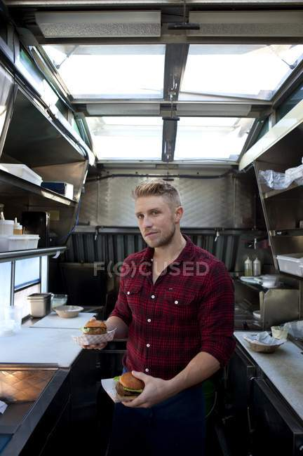 Man preparing hamburgers in fast food truck — Stock Photo