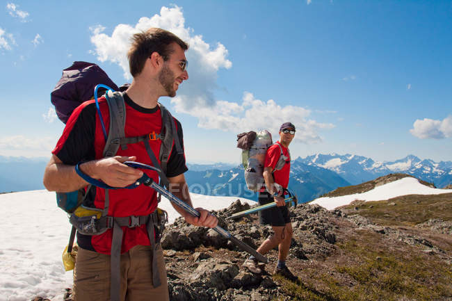 Two backpackers share a laugh while hiking through an alpine meadow. — Stock Photo