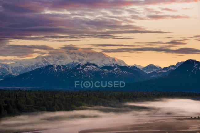 Nevoeiro coberto sobre o rio e evergreens com montanhas no fundo ao pôr do sol, Parque Nacional Denali, Alasca, Estados Unidos da América — Fotografia de Stock