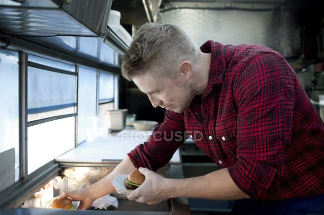 Man selling hamburgers from fast food truck — Stock Photo