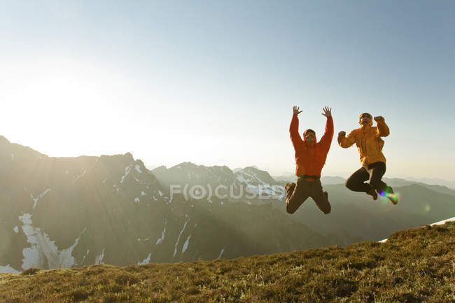 Two hikers jumping in an alpine meadow. — Stock Photo