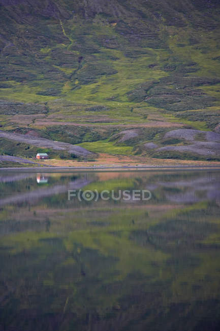 Mountainside reflecting in lake Ljosavatn in north Iceland — Stock Photo