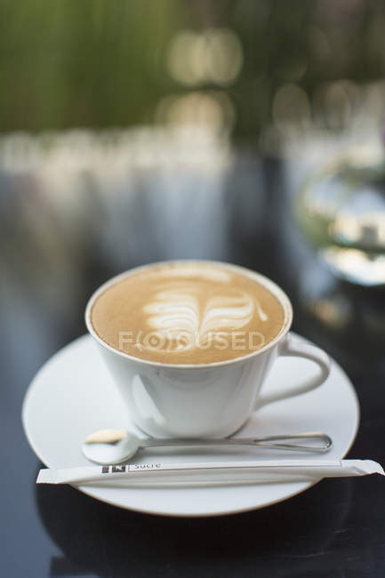 Cup of coffee with leaf shaped foam on glass table — Stock Photo
