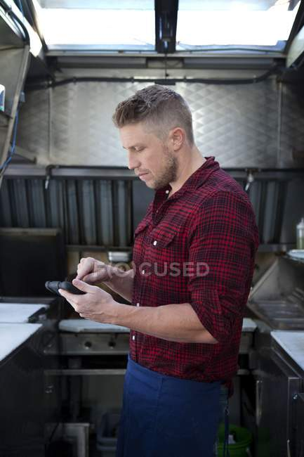 Man using smartphone in fast food truck — Stock Photo