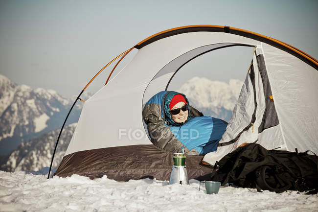 Woman in warm clothing waking up in tent with mountains at background. — Stock Photo