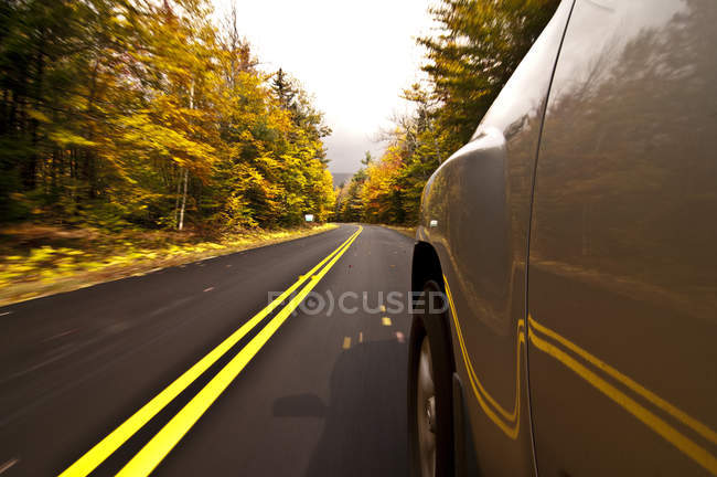 Cropped image of car driving on road around autumn foliage of New Hampshire — Stock Photo