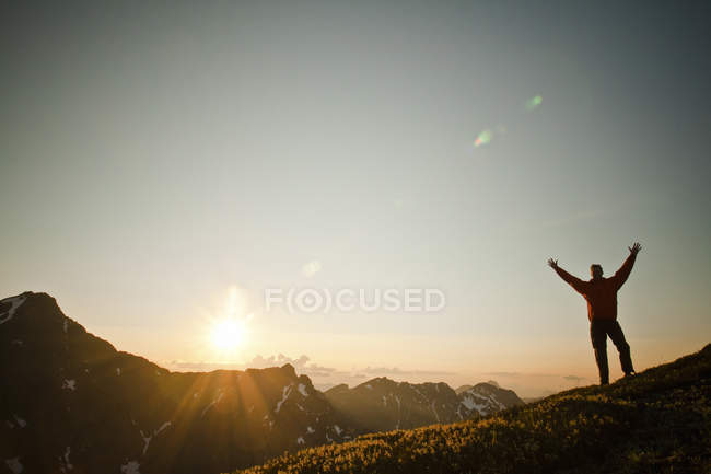 Man standing with his arms up on alpine ridge during sunset — Stock Photo
