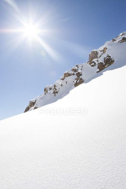 Vue sur la montagne enneigée et un soleil éclatant dans le ciel à Montana. — Photo de stock