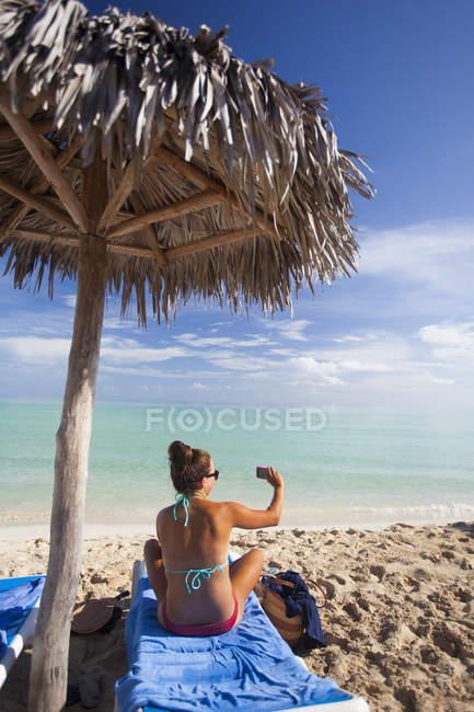Молодая женщина одета в бикини принимает картину пляж qhile расслабиться на отдыхе на Кубе — стоковое фото