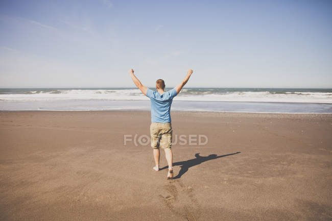 A man raises both fists into the air while walking barefoot on a sandy beach on the Oregon Coast. — Stock Photo