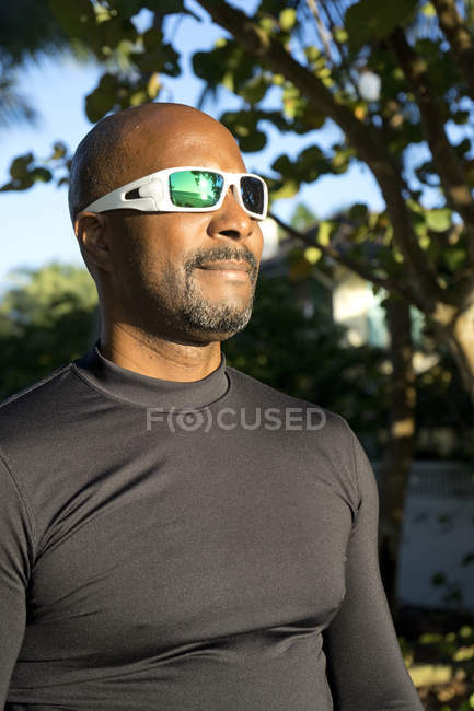 Man in sunglasses and athletic clothing looking away — Stockfoto