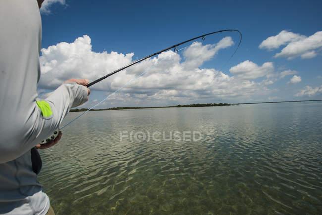Рыбак, борьба рыбы в мелководных теплых водах Флориды Бэй, штат Флорида — стоковое фото