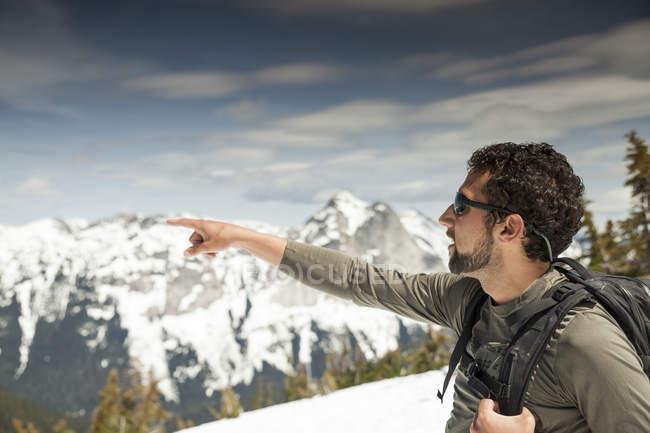 A backpacker points toward an adjacent mountain range while en route toward Needle Peak. — Stock Photo