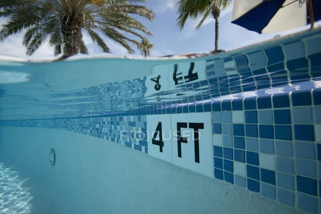 Раскол уровня вид бассейна с 4 ft. маркер и пальмовых деревьев в фоновом режиме — стоковое фото