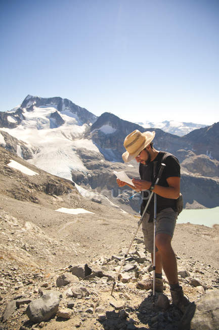 A hiker stops to read directions high in the mountains above Wedgemount Lake in Garibaldi Provincial Park. — Stock Photo